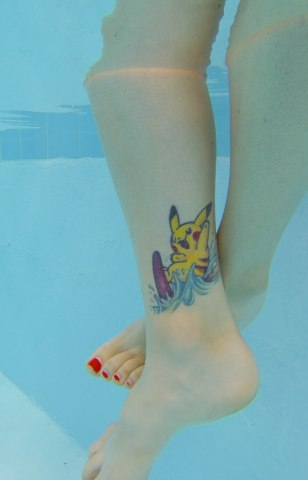 I love this surfing Pikachu tattoo. I hate that the toes got cut off in the photo though.