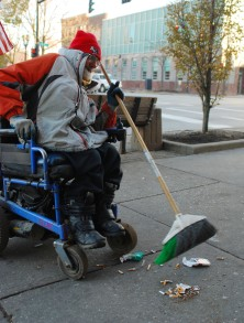 """Georgie sweeps the sidewalk in front of the Zephyr and the Loft downtown. Some of his other jobs he has done around Kent include delivering ice for Diggers and lawn mowing.""""I know guys with legs that don't do as much work as him,"""" says Mary Kay Sitko."""
